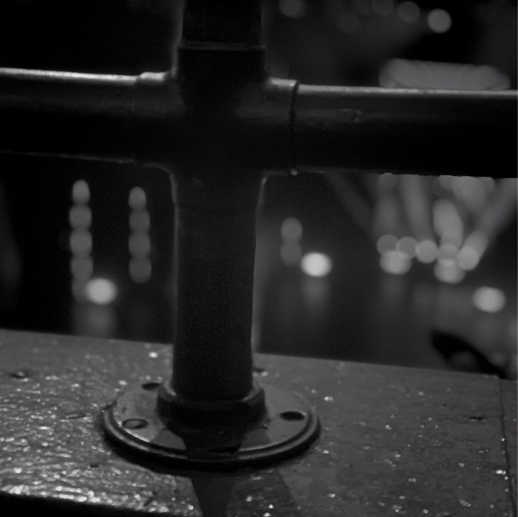Rail on the balcony with blurred lit stage in background.