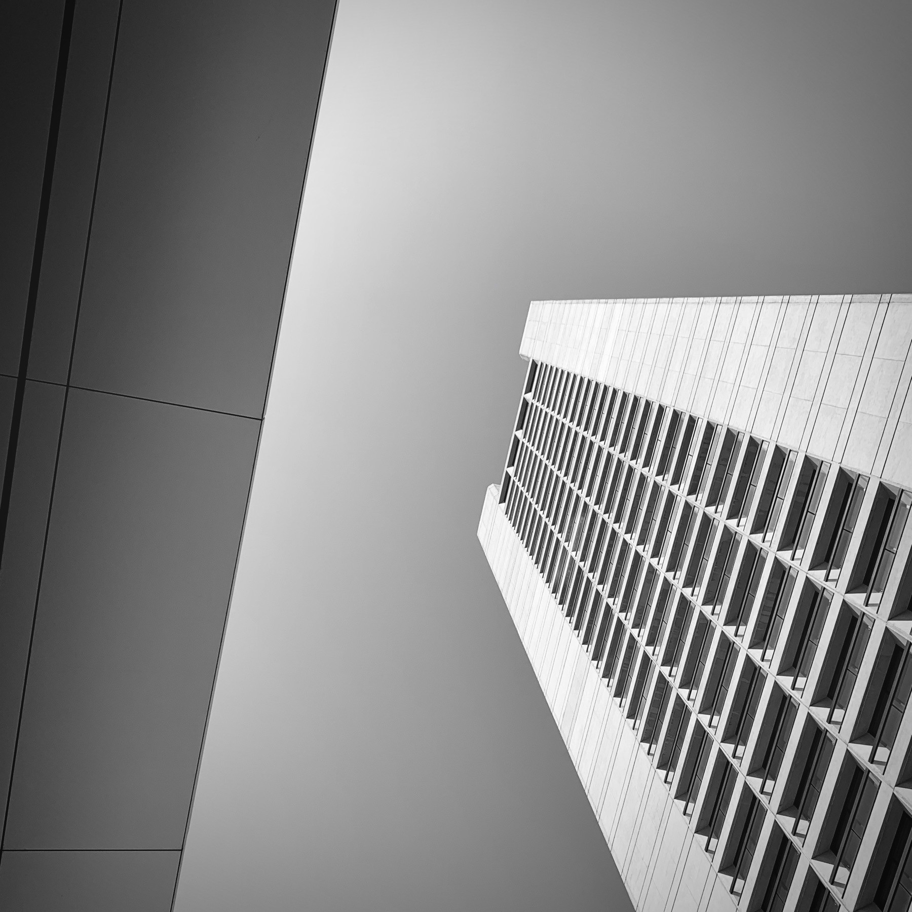 Looking upward at a large skyscraper, black and white.