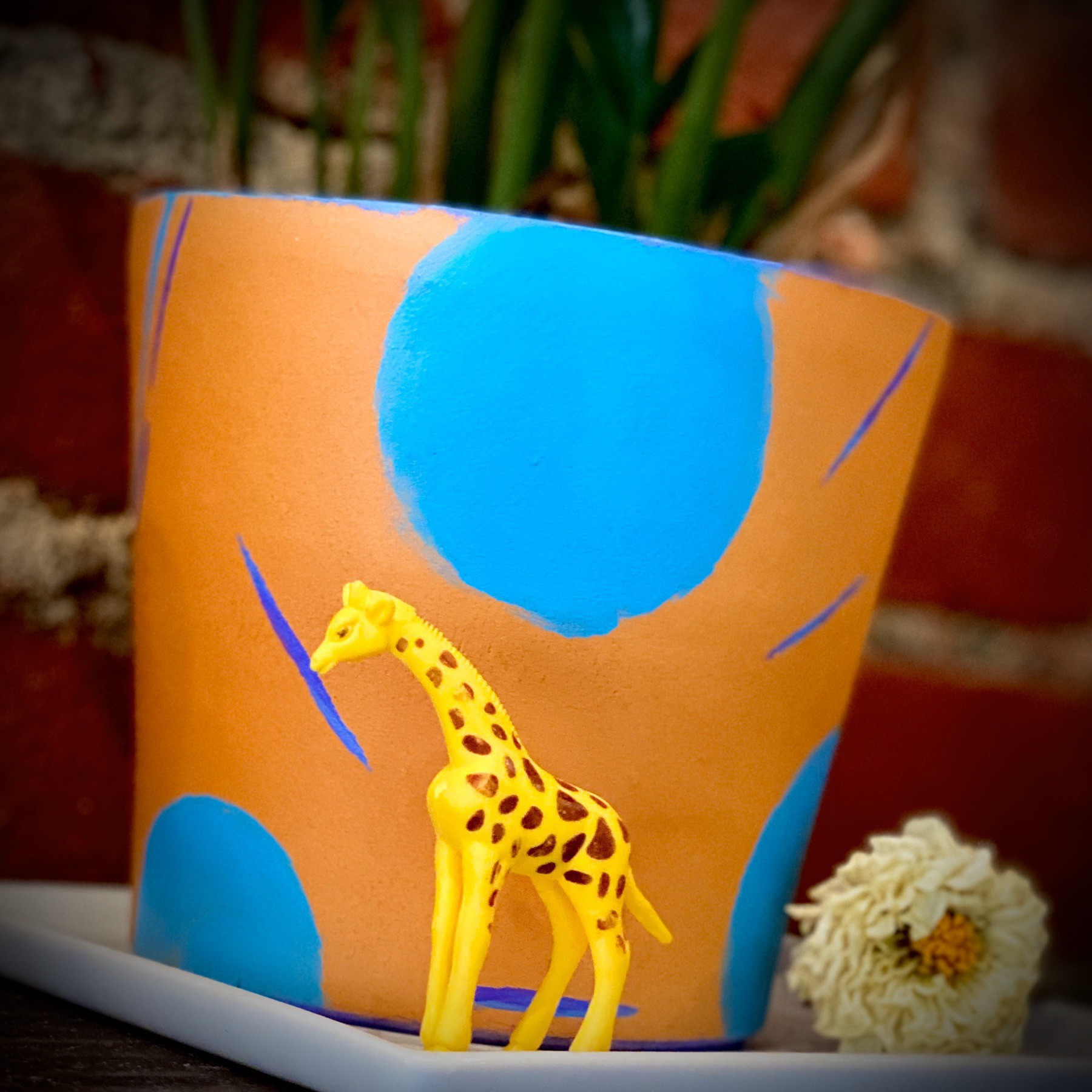 Small Giraffe figurine in front of potted plant.
