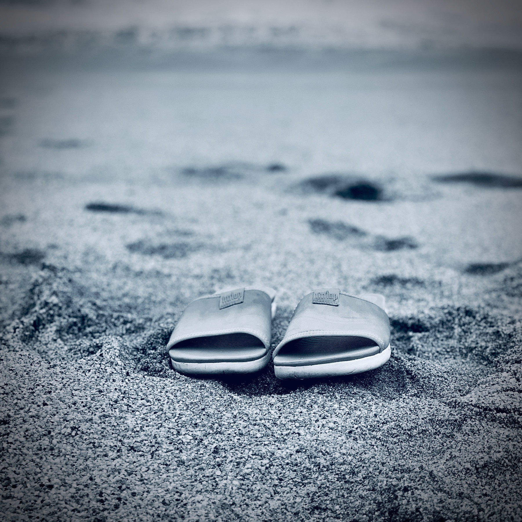 Black and White flip flops on the sand, ocen in the background.