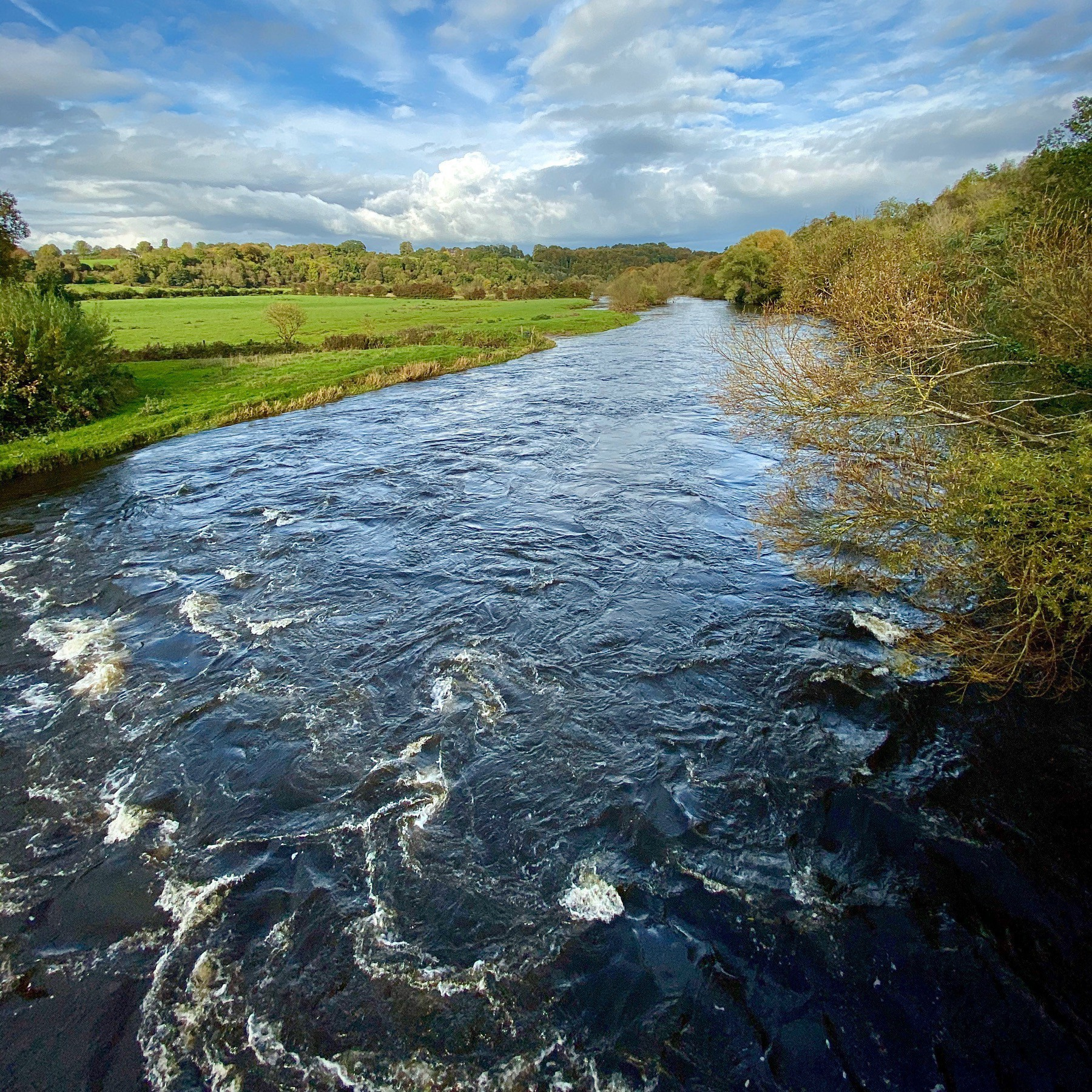 River flowing with blue sky and green pasture. Ireland.