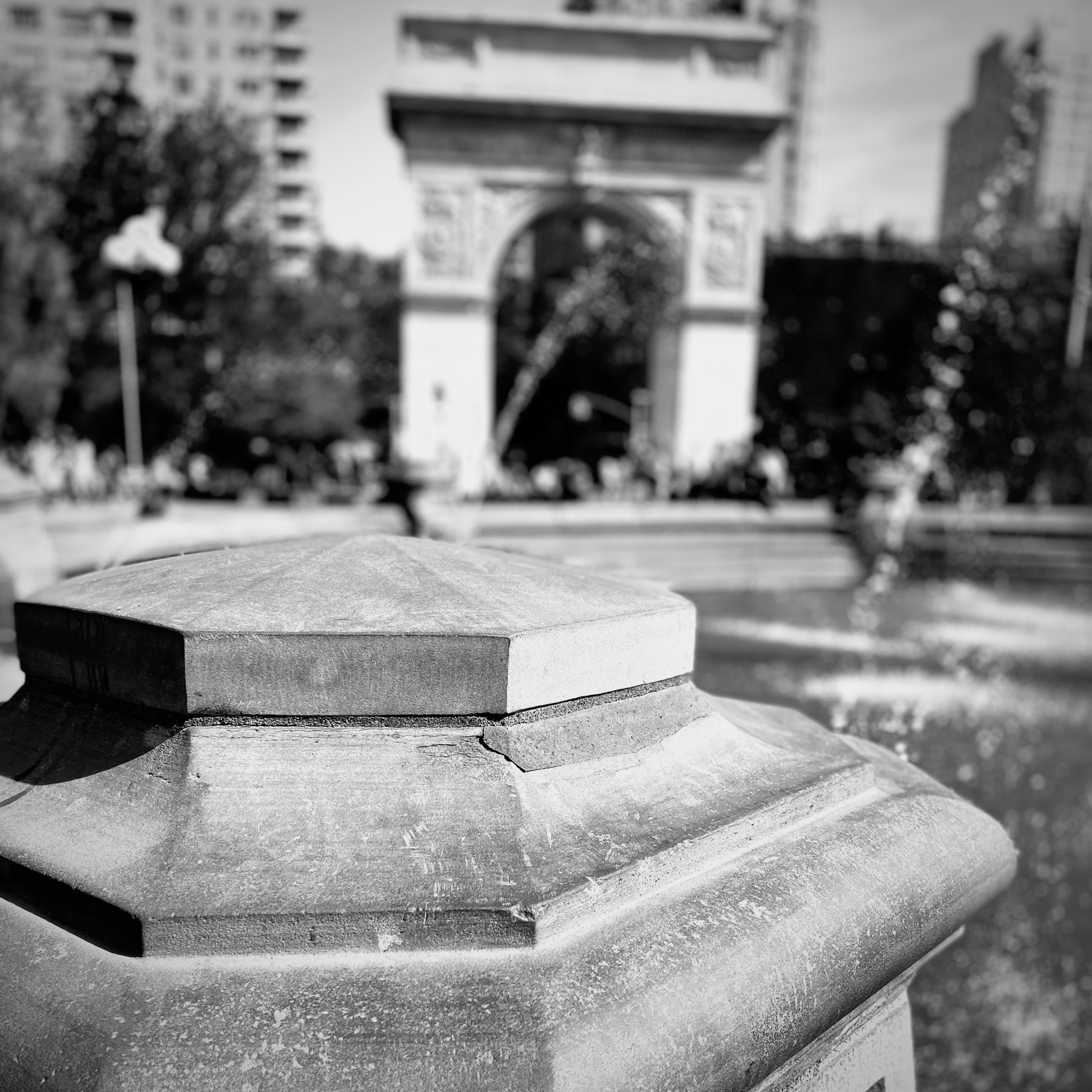 Post from the fountain at Washington Square Park, with arch blurred in background.