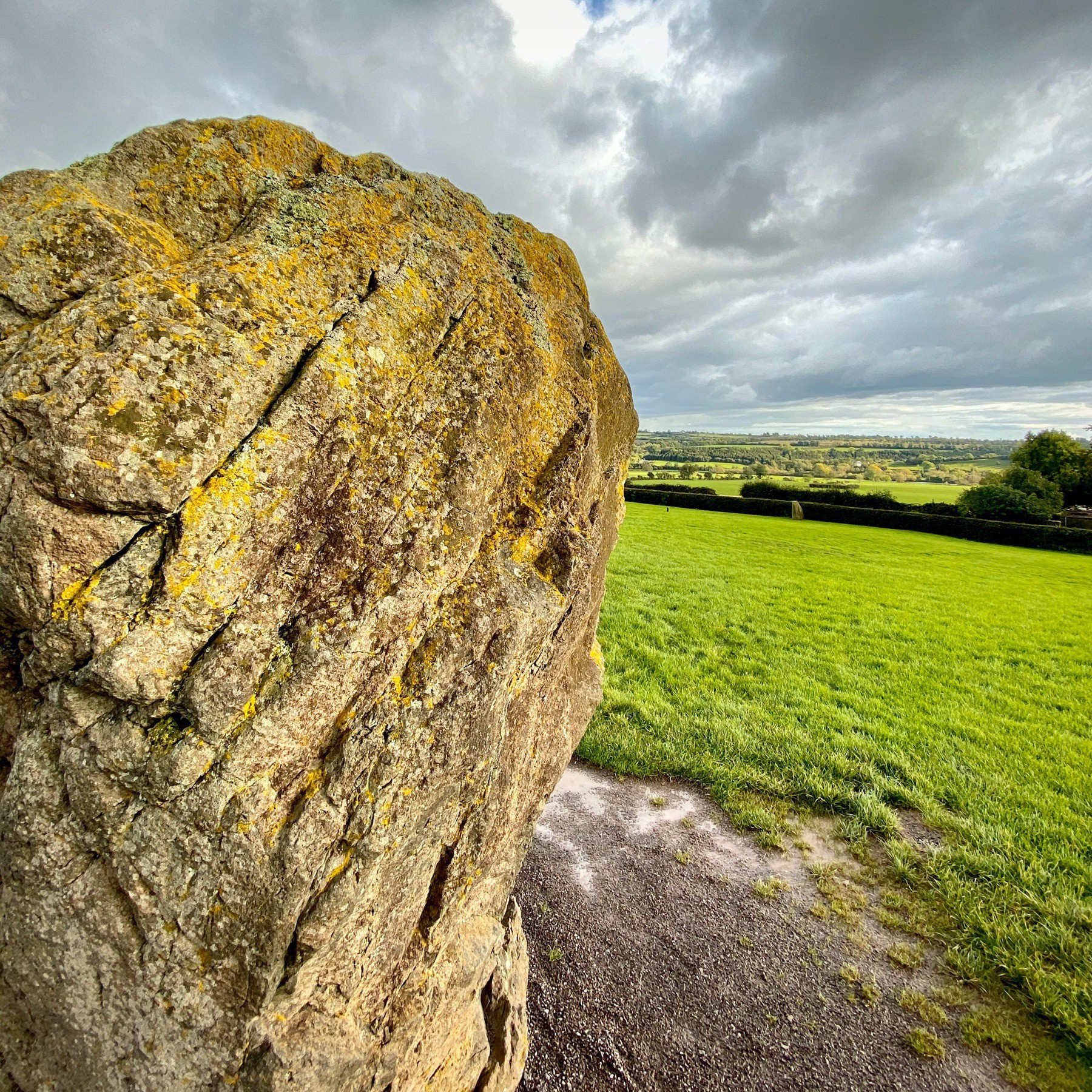 Large boulder in foreground, with green pasture and clouded sky.