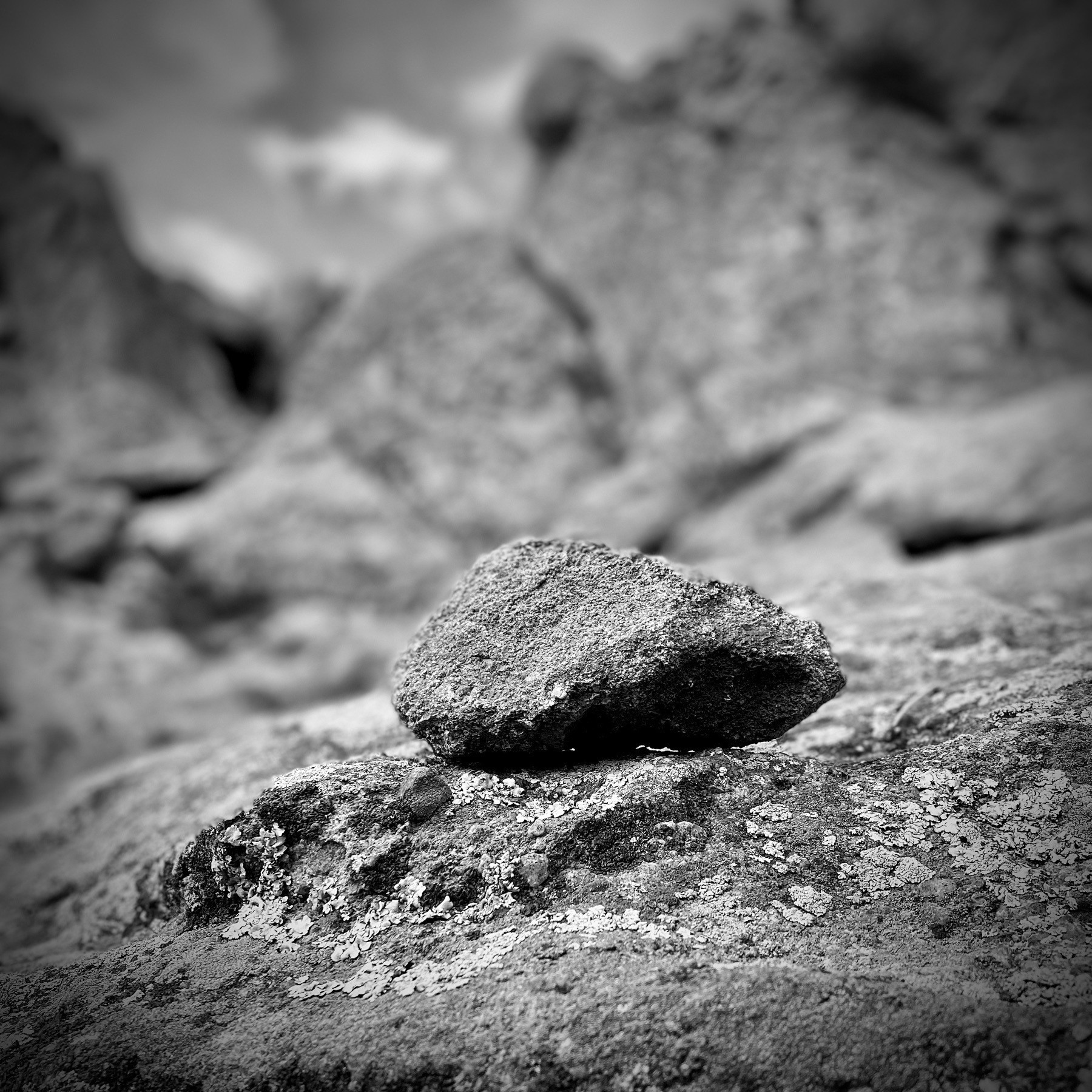 Stone atop boulders, black and white.