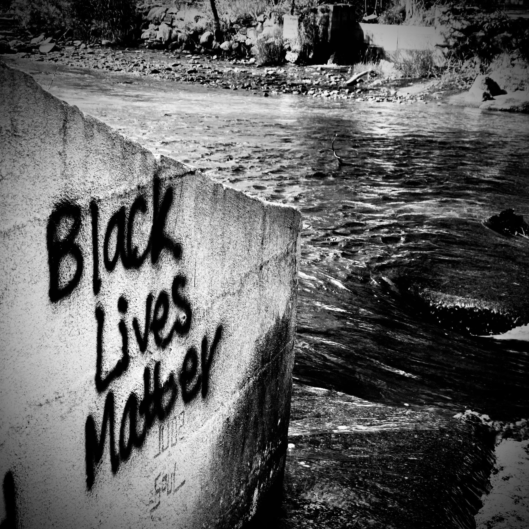 Black Lives Matter spray painted on wall beside a creek