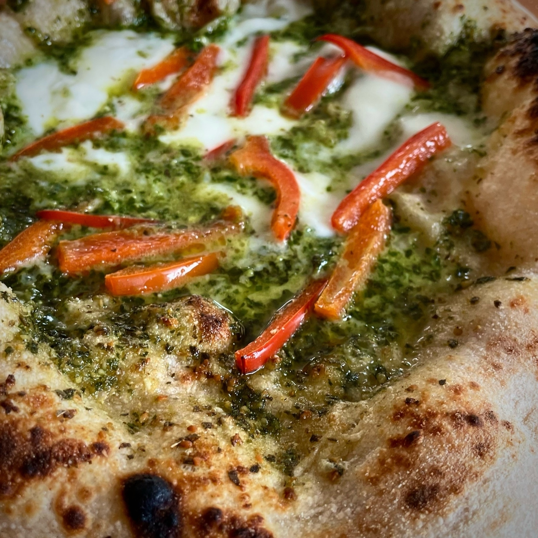 Pizza with pesto, bell peppers.